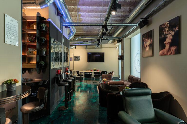 Большой экран и мягкие кресла и столики в каннабис клубе Барселоны